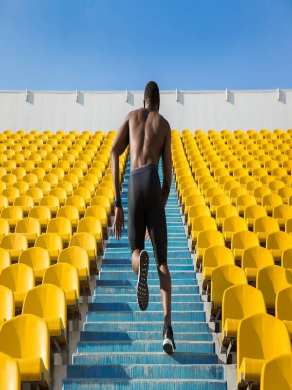 Back view of a sportsman doing speed exercise for muscles